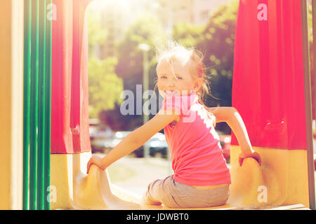 happy little girl on slide at children playground - Stock Photo