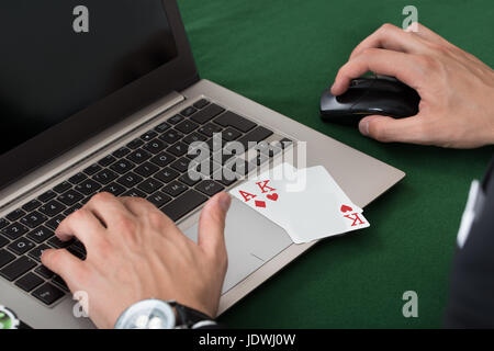 Cropped image of businessman with cards using laptop at desk in office - Stock Photo