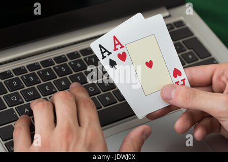 Cropped image of businessman holding cards while using laptop in office - Stock Photo