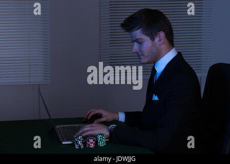 Side view of businessman working late on laptop by stacked poker chips at desk in office - Stock Photo