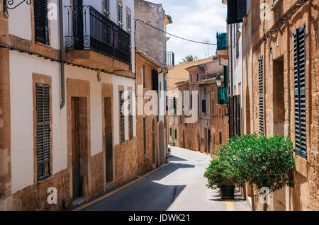 Alcudia, Mallorca, Spain - May 23, 2015: Narrow street of historical town part of Alcudia with its traditional house - Stock Photo