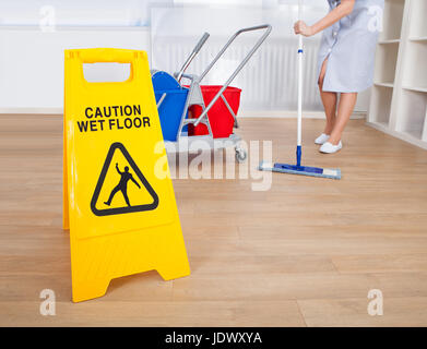 Close-up Of Warning Sign On Wet Floor - Stock Photo