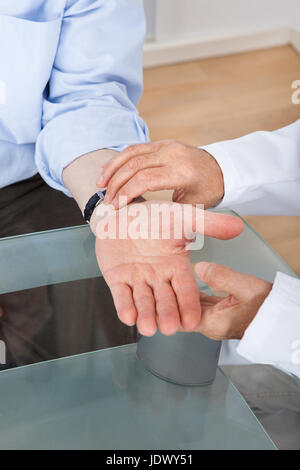 Cropped image of doctor taking senior man's pulse at desk in clinic - Stock Photo