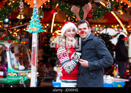 Man and woman or  a couple  or friends during advent season or holiday in front of a carousel or 'marry-go-round' - Stock Photo