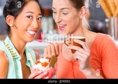 Young female customers or friends in an ice cream parlor with ice cream cornet - Stock Photo