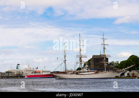 Three-masted barque rigged tall ship Statsraad Lehmkuhl with small cruise ship Expedition moored in Vågen harbour - Stock Photo