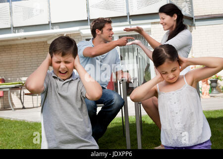 Little children covers their ears as their parents argue loudly behind - Stock Photo