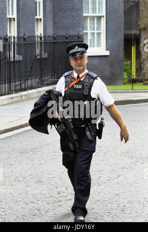 Law & Order, Police officer carrying firearm in Downing Street, Westminster, London, England. - Stock Photo