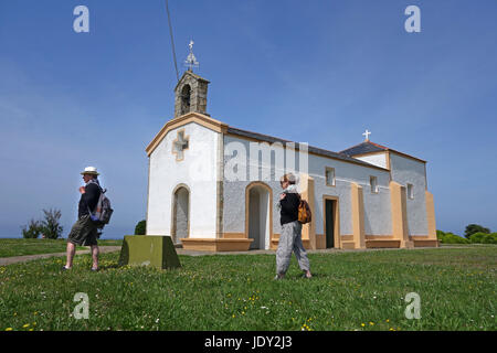 Walkers on the pilgrims walk at Puerto de Vega, capilla de La Atalaya in Northern Spain  Asturias, Spain - Stock Photo