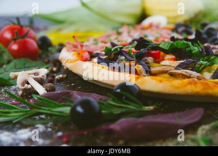 Italian pizza with mozzarella, black olives, prosciutto and tomatoes - Stock Photo