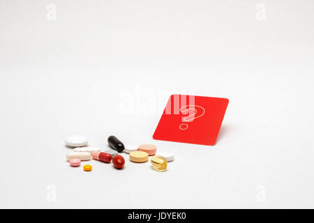 verschiedene bunte Tabletten mit rotem Fragezeichen-Schild, isoliert - Stock Photo