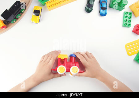 Top view on child's hands playing with toy train and many toys on the white table background. - Stock Photo