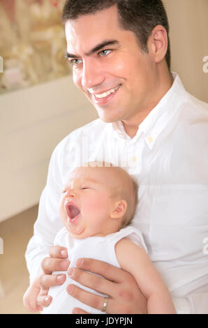 Happy father with yawning daughter on hands at home, enjoying bedtime, cheerful parenthood, love and happiness concept - Stock Photo
