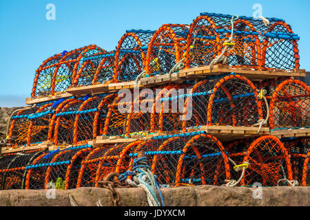 Close up of large pile of colourful lobster pots or creels on harbour side on sunny day with blue sky,North Berwick, - Stock Photo