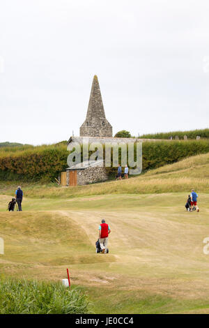 Golfers playing a round of golf on an overcast day at the world renowned St. Enodoc Golf Club in Cornwall with St. - Stock Photo