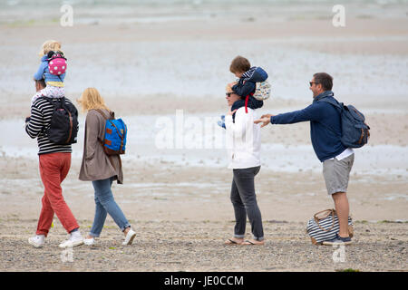Family enjoying a walk along the beach at Daymer Bay Beach in Cornwall, England, UK on an overcast summers day - Stock Photo