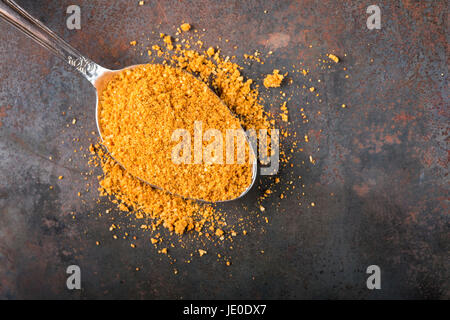 Spoon filled with spices for the preparation of roast on rusty background with copy space - Stock Photo
