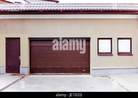 Closed Brown Corrugated Metal Garage Gate With Doorway And Two Windows On Plaster Wall