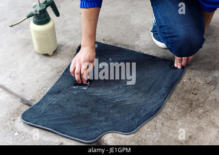 Details of automobile cleaning - male using professional chemical solutions to clean car floor mats - Stock Photo