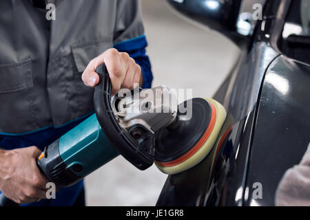 Close-up of hands worker using polisher to polish a black car body in the workshop - Stock Photo