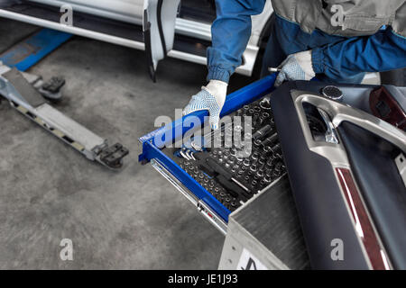 The mechanic selects the tool. tools for service station. spanners and socket nozzles - Stock Photo