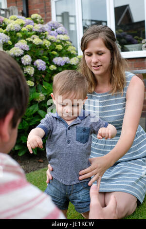 One year old baby boy taking first steps - Stock Photo