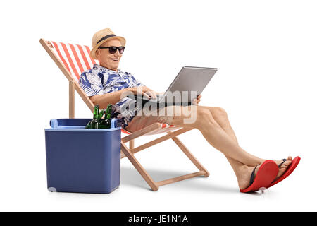 Elderly tourist with a laptop sitting in a deck chair next to a cooling box filled with bottles of beer isolated - Stock Photo