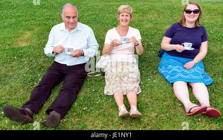 Three people at a local village fete sitting on the grass enjoying a cup of tea on a hot summers day, Herriard, - Stock Photo