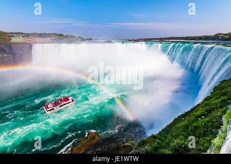 Hornblower Boat Full of Tourists Under Rainbow Sprayed By Horseshoe Waterfall, Niagara Falls, Ontario, Canada - Stock Photo