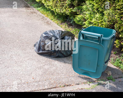 green food recycling bin open outside on front pavement with black tied bag - Stock Photo