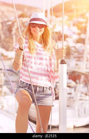 Luxury photoshoot on sailboat, cute blond model posing in mild yellow sunset light, summer vacation concept - Stock Photo