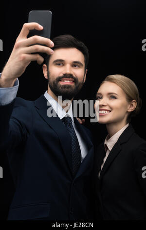 smiling business people taking selfie on smartphone isolated on black - Stock Photo
