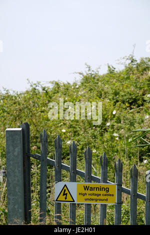 17th June 2017 - Caution high voltage warning signs on a secure metal palisade fence. - Stock Photo