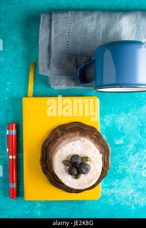 Colorful still life with cake on the cyan background vertical - Stock Photo