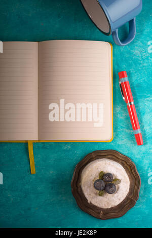 Cake , cup , notebook , napkin and pen on the cyan background vertical - Stock Photo
