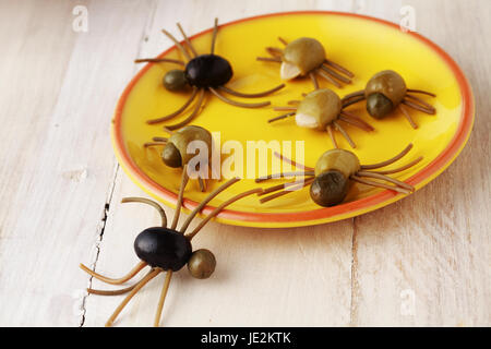 Creepy crawly Halloween spider snacks for a party celebration made from black and green olives with Italian spaghetti - Stock Photo