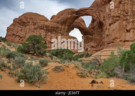 Fascinating close placement of natural sandstone double arches reflects wild, unique beauty of red sand and stark - Stock Photo