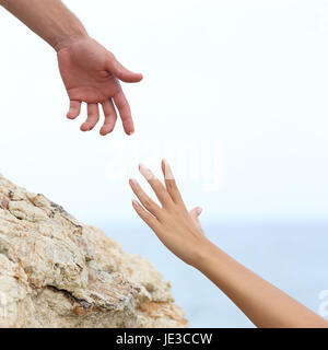 Man and woman hands helping concept with the sea in the background - Stock Photo