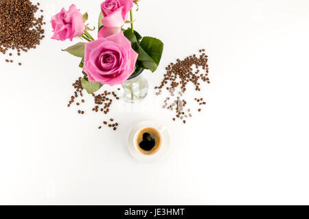 Top view of beautiful pink roses in vase and cup of espresso coffee - Stock Photo