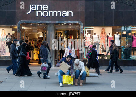 LONDON, ENGLAND - JULY 12, 2016 A man helps his wife pack purchases near Jane Norman - Stock Photo