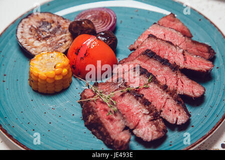 Pieces of beef and vegetables cooked on the grill. - Stock Photo