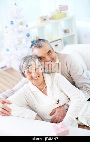 Joyful seniors looking at camera on background of Christmas tree - Stock Photo