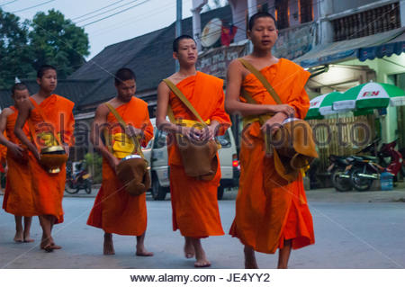 Young monks wearing ochre coloured robes collecting alms (tak bat) in Luang Prabang, Laos. In the early morning - Stock Photo