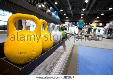 Colorful medicine balls on rack in health club and people exercising in background - Stock Photo