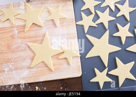 Star shaped Christmas cookie dough on cutting board and baking sheet, from above. - Stock Photo