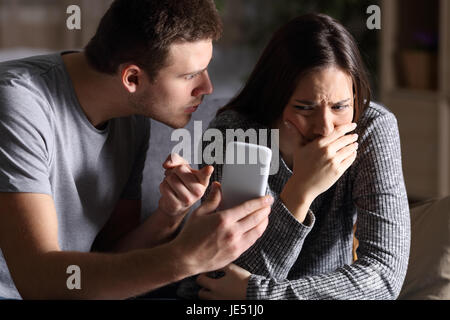 Boyfriend asking for an explanation to his cheater sad girlfriend sitting on a couch in the living room in a house - Stock Photo