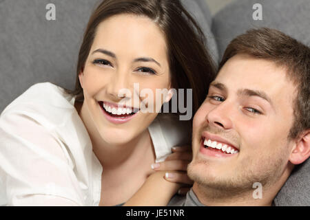 Happy couple with perfect teeth and white smile lying on a couch and looking at you - Stock Photo