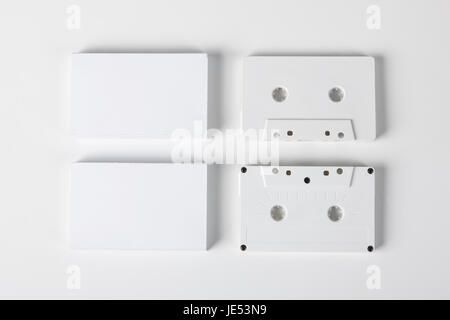 Blank audio cassettes on white background with blank packaging - Stock Photo
