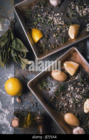 Baking dish with raw flounders and seasoning vertical - Stock Photo