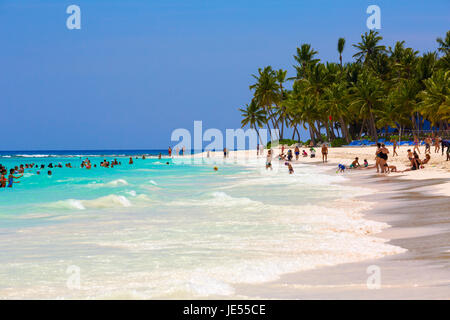 beach of the island Saona with tourists on the hot summer day. - Stock Photo